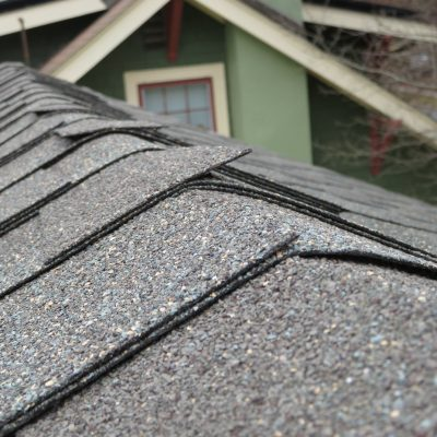 Improper shingles are used at this roof ridge, notice how the edges are stick up