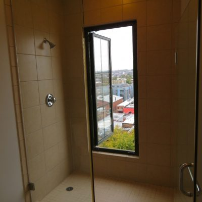 This bathroom window, very close to the slippery shower floor in a top level apartment opens completely out without any safety barrier.